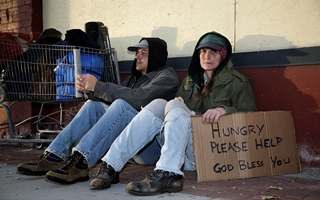 Image of two homeless people sitting on the street